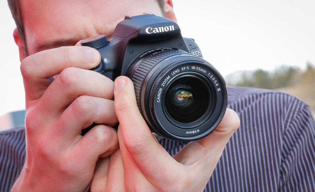 Зеркальный фотоаппарат в руках.